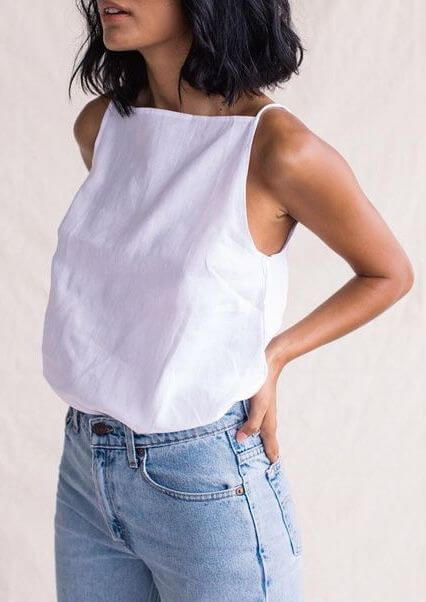 lady in white tank and blue jeans