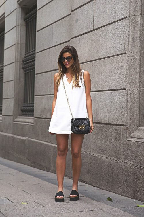 lady in white dress carrying a black purse