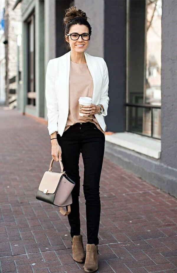 lady holding a cup of coffee with light top and black pants