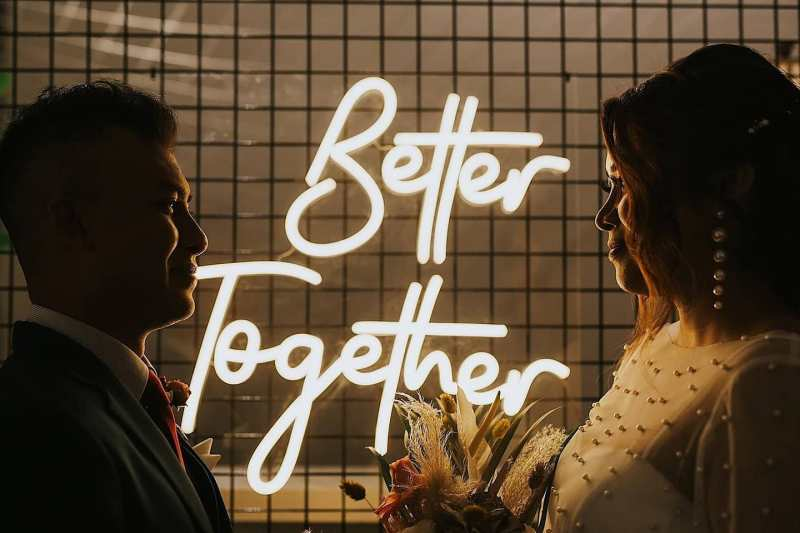 'Better Together' neon lights between a wedding couple smiling at each other
