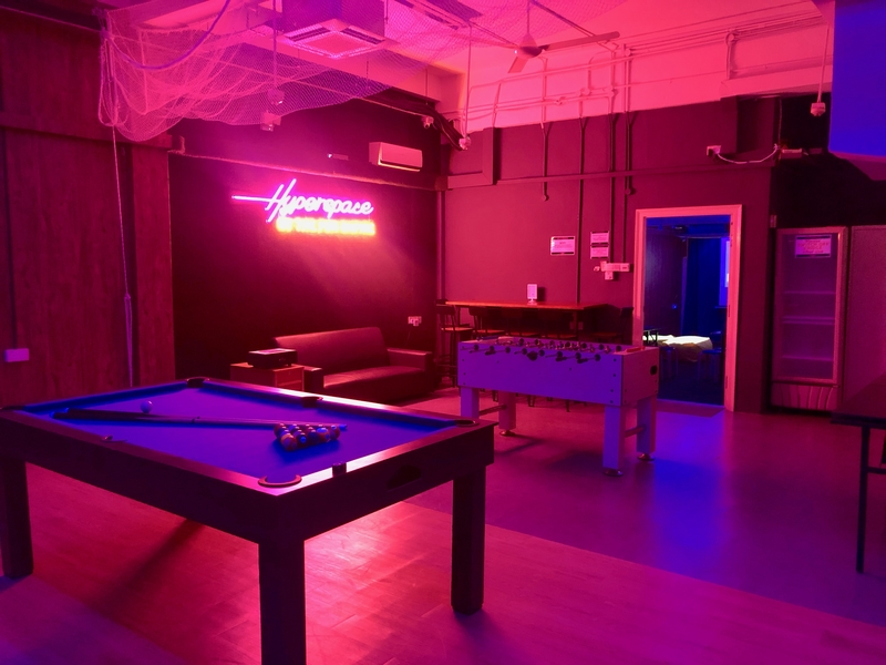 A room with pools table and neon pink 'hyperspace' lights