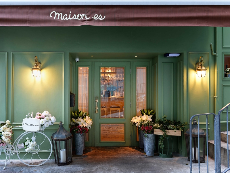 green entrance with bike and flowers of a restaurant