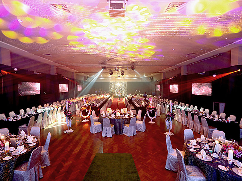 disco lights in a function hall with tables and chairs