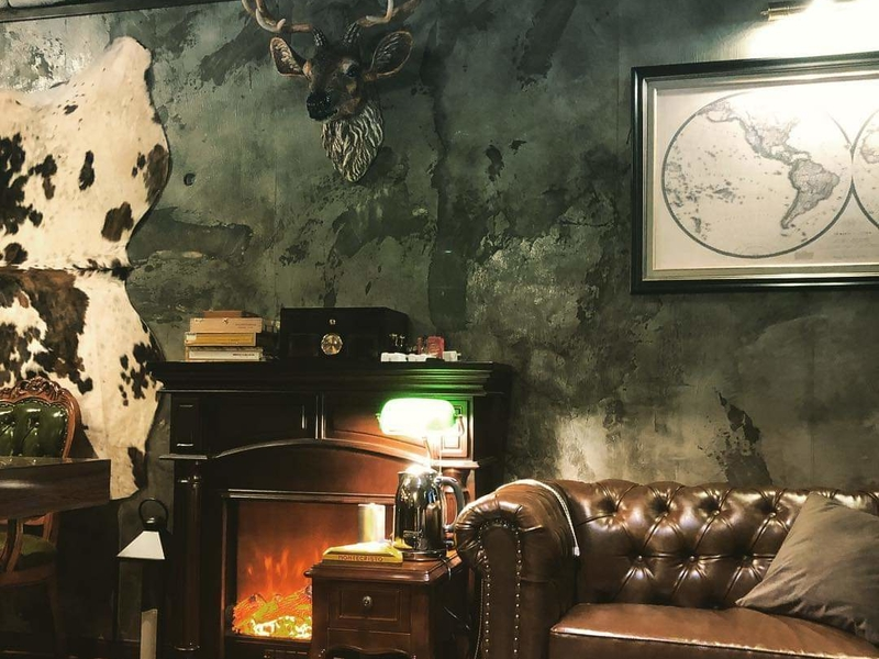 Dark wall with decorative elements and partial view of brown leather couch