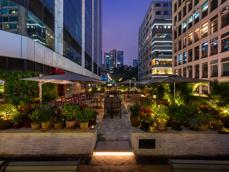 Outdoor area surrounded by tall buildings and potted plants