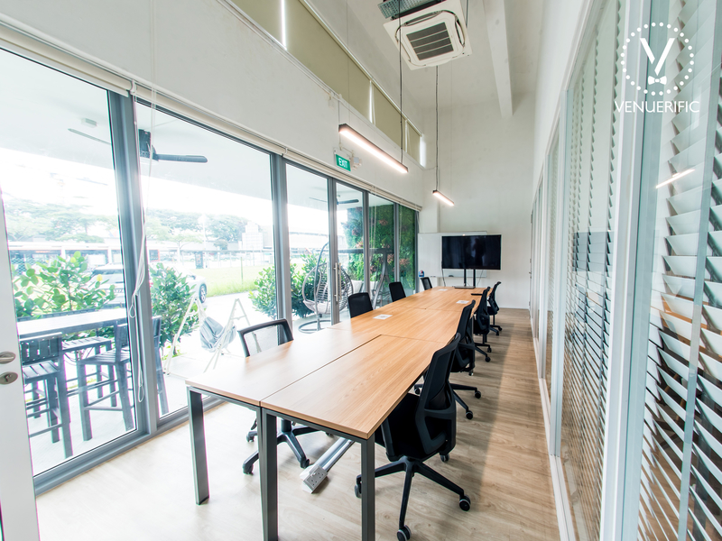 Indoor meeting room with long table and chairs with attached screen for presenting