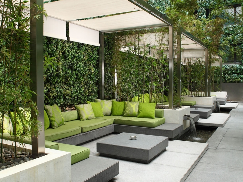 green cushions around a seating area with greeneries