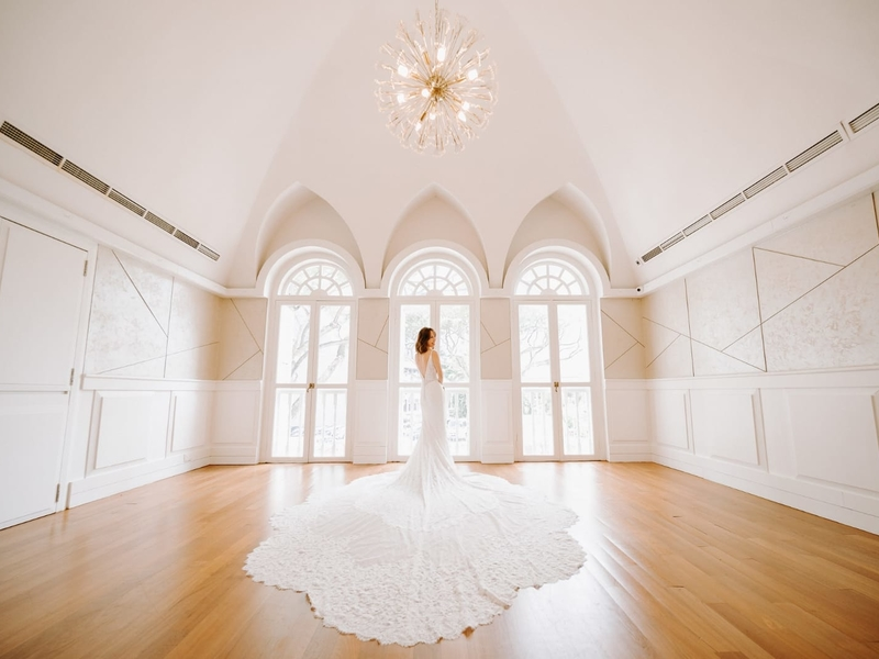 bride in a gown at a white room for a photo shoot
