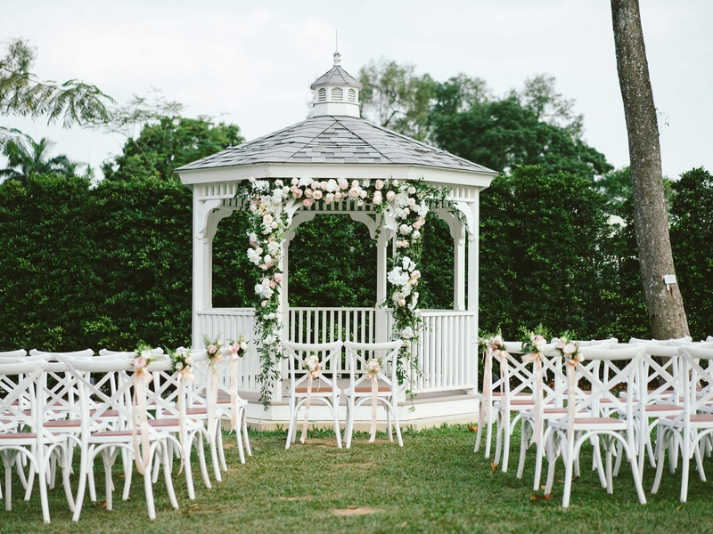 Outdoor event gazebo lined with floral decor and surrounded by seating.