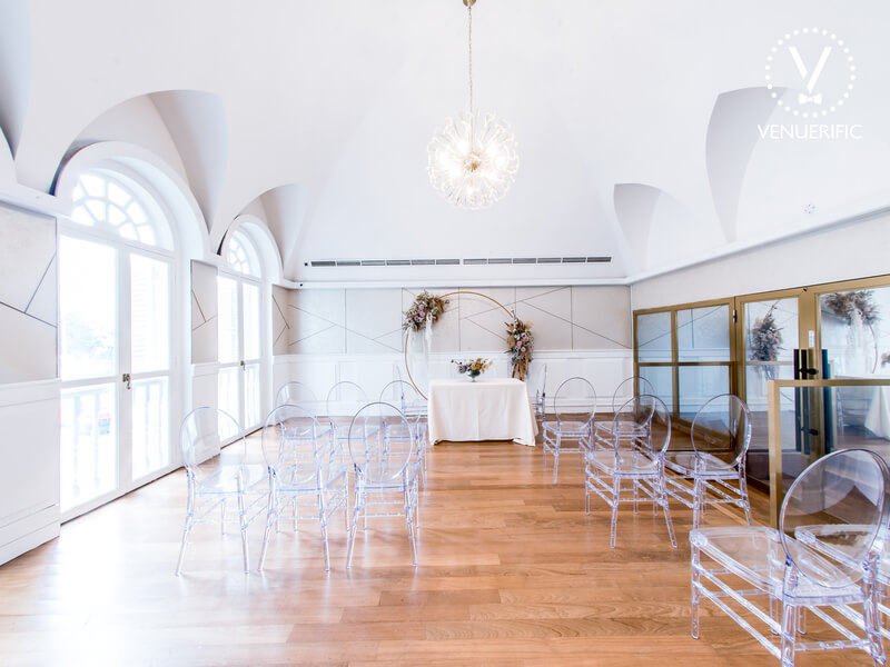 White wedding venue set up with transparent plastic chairs