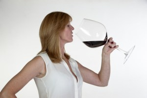 Woman drinking from a very large glass of red wine