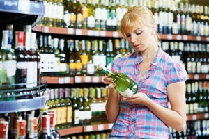woman choosing and shopping wine at supermarket