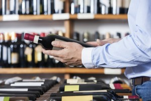 Midsection Of Customer Holding Wine Bottle