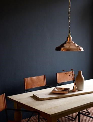 Bronze suspension lamp and decorations on the table, great combination with the dark wall