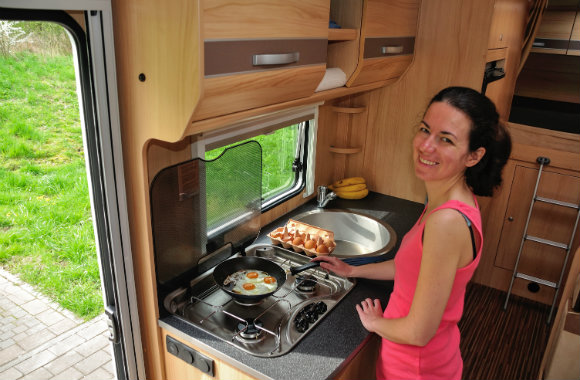 woman cooking inside an RV rental
