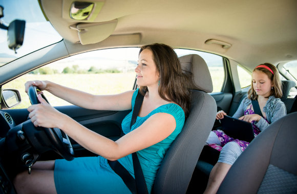 woman-driving-the-car-while-her-daughter-playing-an-ipad
