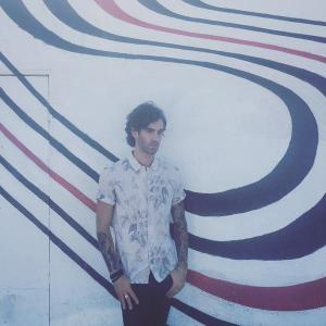 "Zac Barnett in front of the Elliott Smith's ""Figure 8"" album cover wall in LA."
