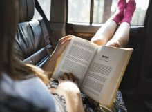 girl reading a book in a car