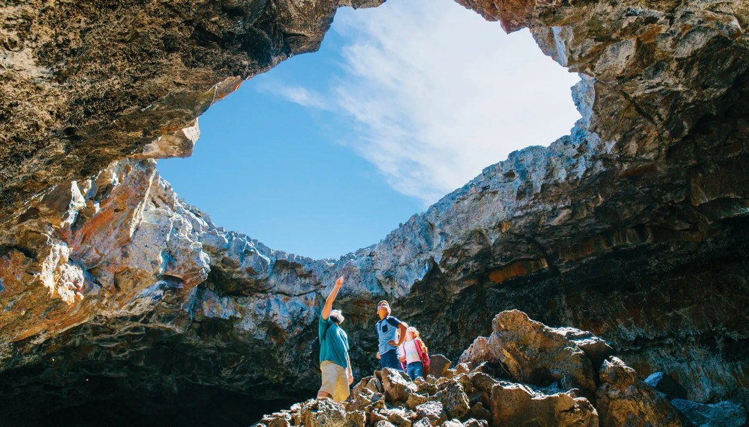 A family explores a cave at Craters of the Moon National Monument and Preserve