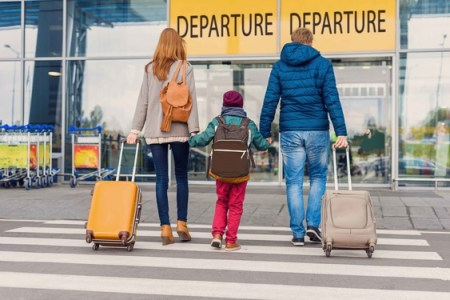 A young family of three at the departure lounge of an airport
