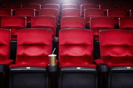 Empty red cinema seats with a bowl of popcorn
