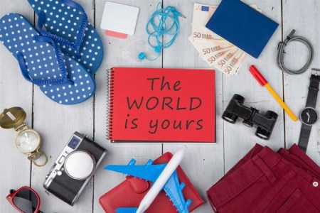 """Christmas adventure props - plane, passport, money, camera, compass, note pad with text """"The World is yours"""", binoculars, jeans, watch, flip flops, wallet on white wooden table"""