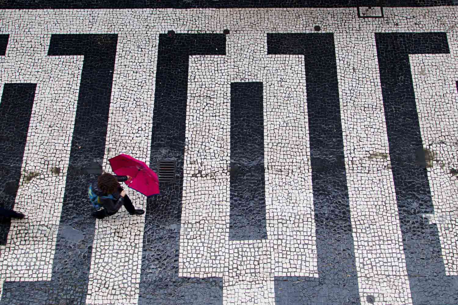 A bright pink umbrella and black and white tiles in Porto