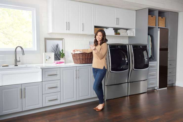 woman with laundry basket in laundry room with LG washer and dryer