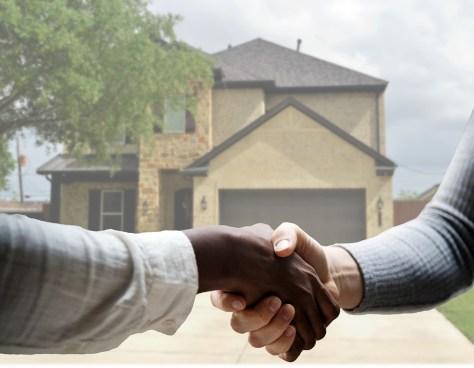agente de venta de inmuebles estrecha mano con su cliente