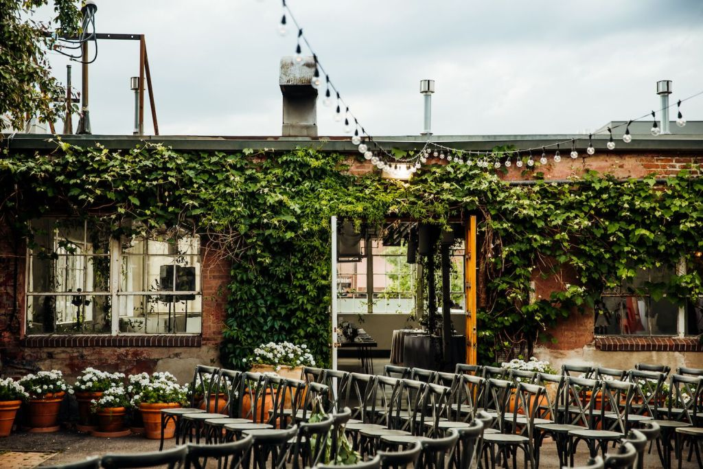 Blanc Venue Colorado, outdoor space pictured with hanging lights, greenery, seats, and flowers. Warm toned picture.