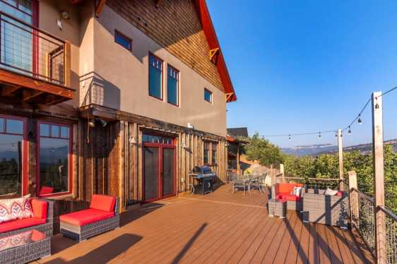 Durango Valley Views Airbnb Wedding Vanue, large house, beige and red theme, rustic interior, surrounded by blue skies and greenery. Hanging lights on side, backyard image.