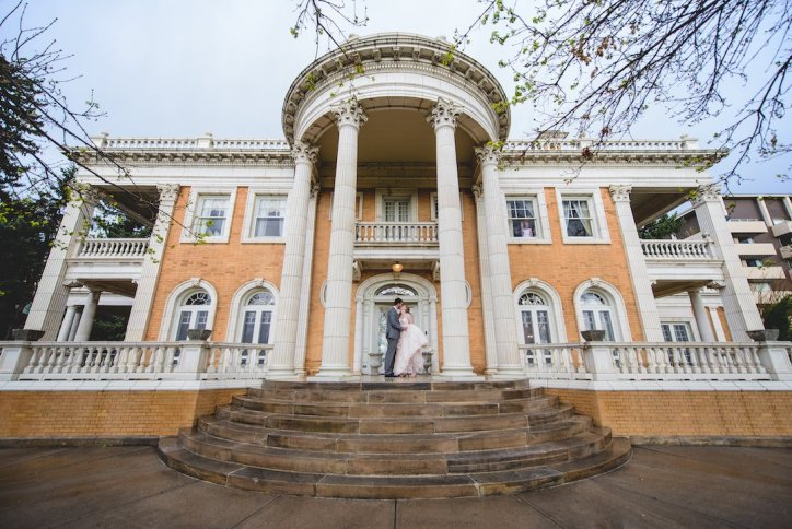 Longshot capture of Grant Humphries Mansion in Denver, Colorado. Large mansion, tan coloured with white detailing, large white columns. Bride and groom stand together in the middle of the photo, in front of the mansion doors.