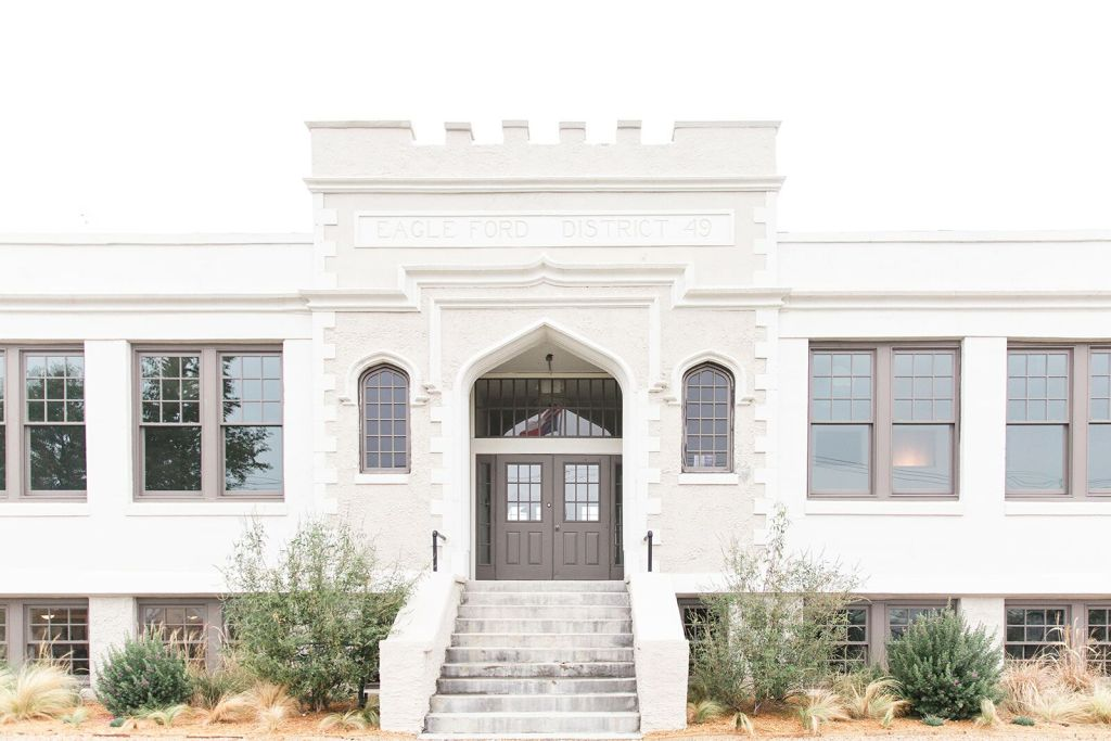 Exterior of Schoolhouse wedding venue, Dallas, stunning white architecture, castle like rooftop.