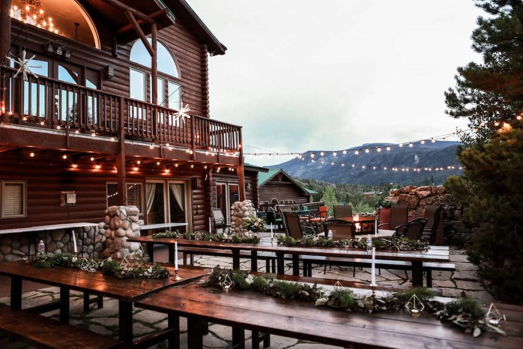 Grand Lake Mountain House Airbnb, lodge style house, overlooking rocky mountains, with lighting and outdoor decor.