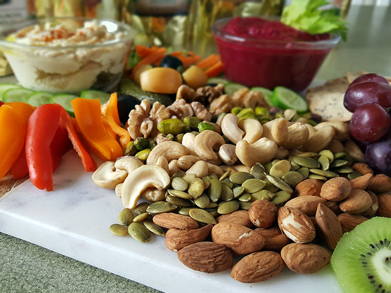 A photo of a selection of nuts and seeds, sliced veggies, dips, and other vegan foods.