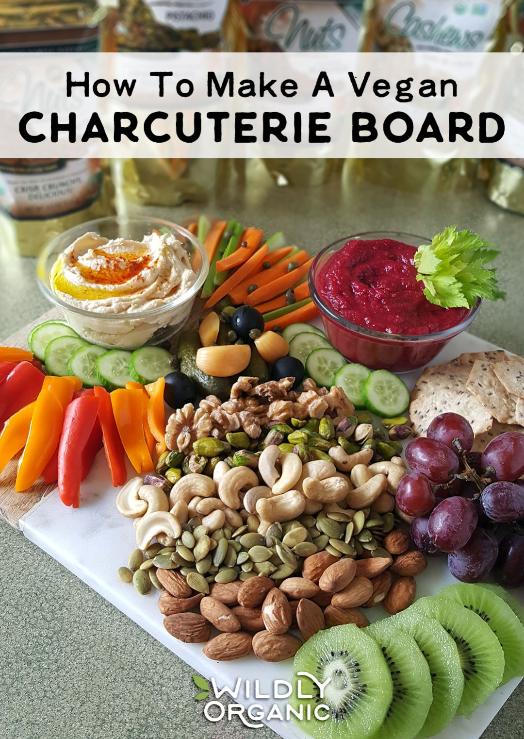 Photo of sliced veggies, nuts, dips, crackers, fruit, and more on a marble cutting board. | Charcuterie boards are fantastic for parties, movie night, and snacky weekend afternoons. They are also typically made with meats and cheeses. Why let the meat eaters have all the fun? I'll show you how to make a vegan charcuterie board that is beautiful, healthy, and will be sure to wow your family and friends!