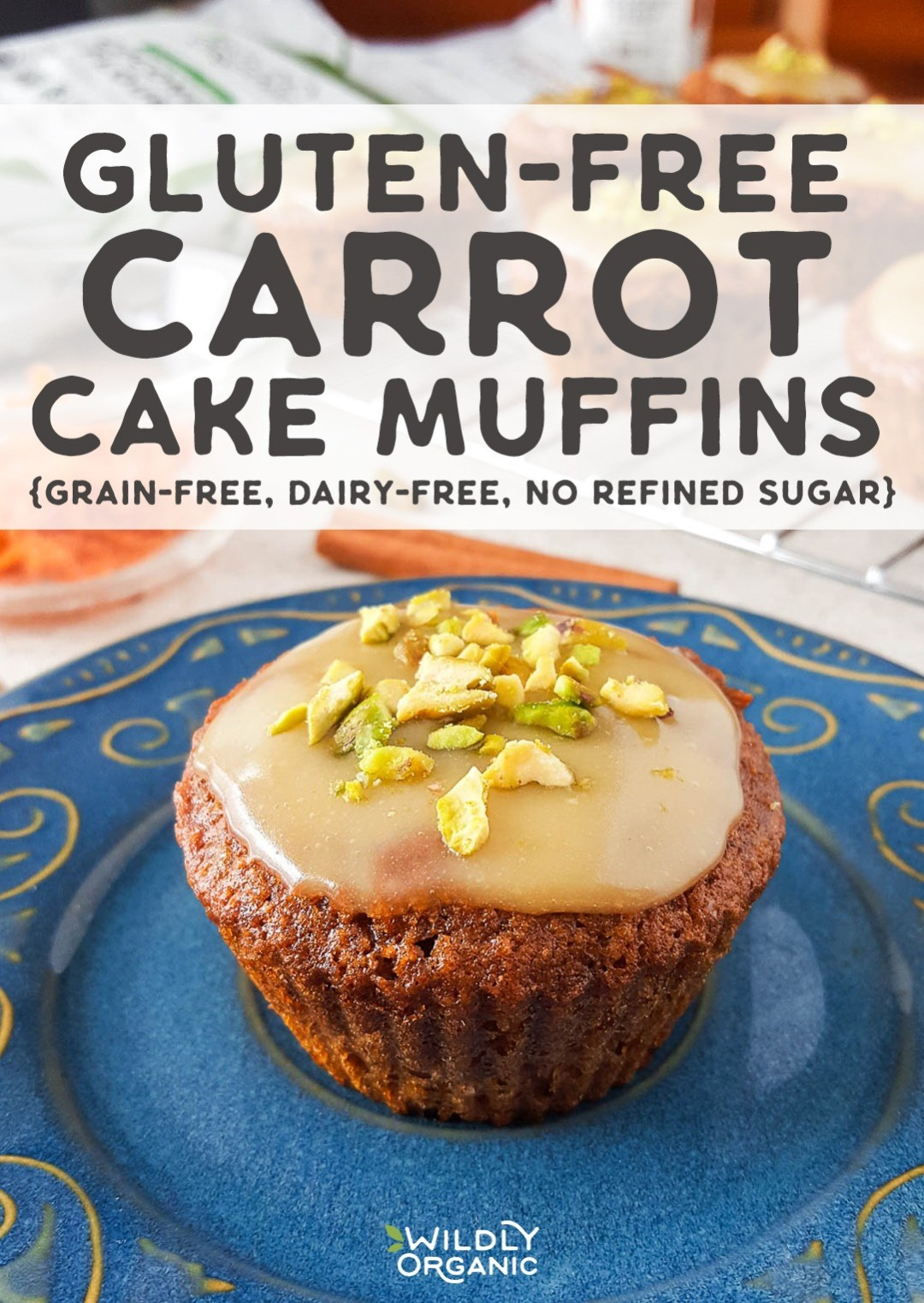 Photo of a gluten-free carrot cake muffin on a blue plate topped with a white chocolate glaze and crushed pistachios.