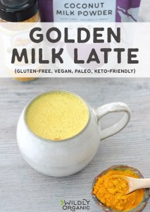 Photo of golden milk latte in a ceramic mug with a dish of turmeric next to it.