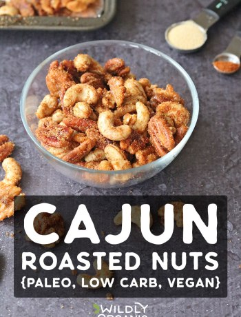 Photo of cajun spiced nuts in a glass bowl and scattered around.