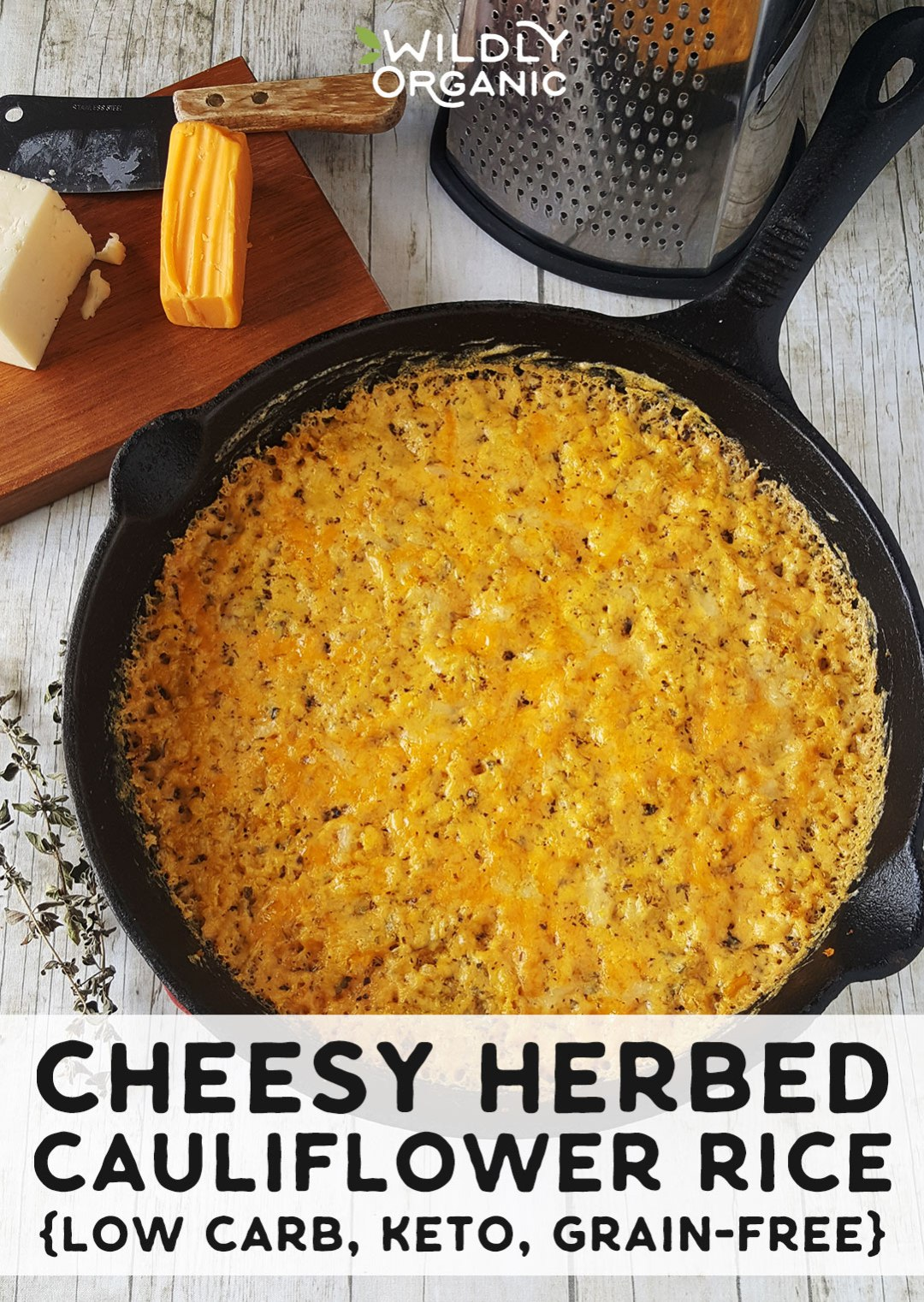 Photo of Cheesy Herbed Cauliflower Rice in a cast iron skillet with cheese, a cutting board, knife, and grater in the background.