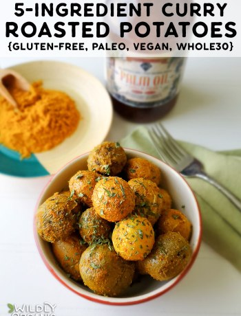 A photo of a bowl of 5-ingredient curry roasted potatoes with a jar of red palm oil and a late of curry powder.