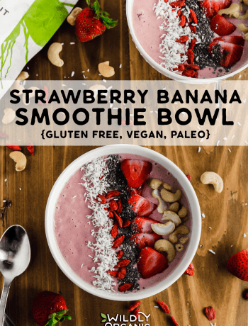 A photo of two strawberry banana smoothie bowls topped with shredded coconut, goji berries, chia seeds, strawberries and cashews on a wooden table.