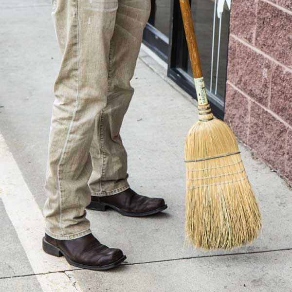 Cleaning up job site with broom