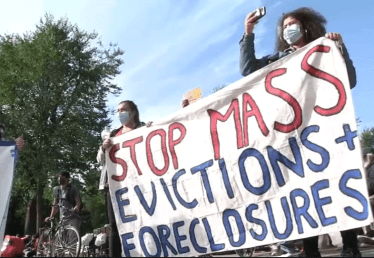 """Two people with a protest banner that says """"Stop Mass Evictions + Foreclosures"""""""