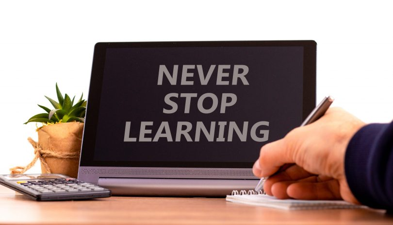 Never stop learning symbol. Tablet with words \'Never stop learning\'. Businessman holds pen, house plant. Beautiful white background. Business, educational, never stop learning concept, copy space.