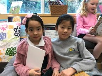 Little school student with their Grade 3 reading buddy