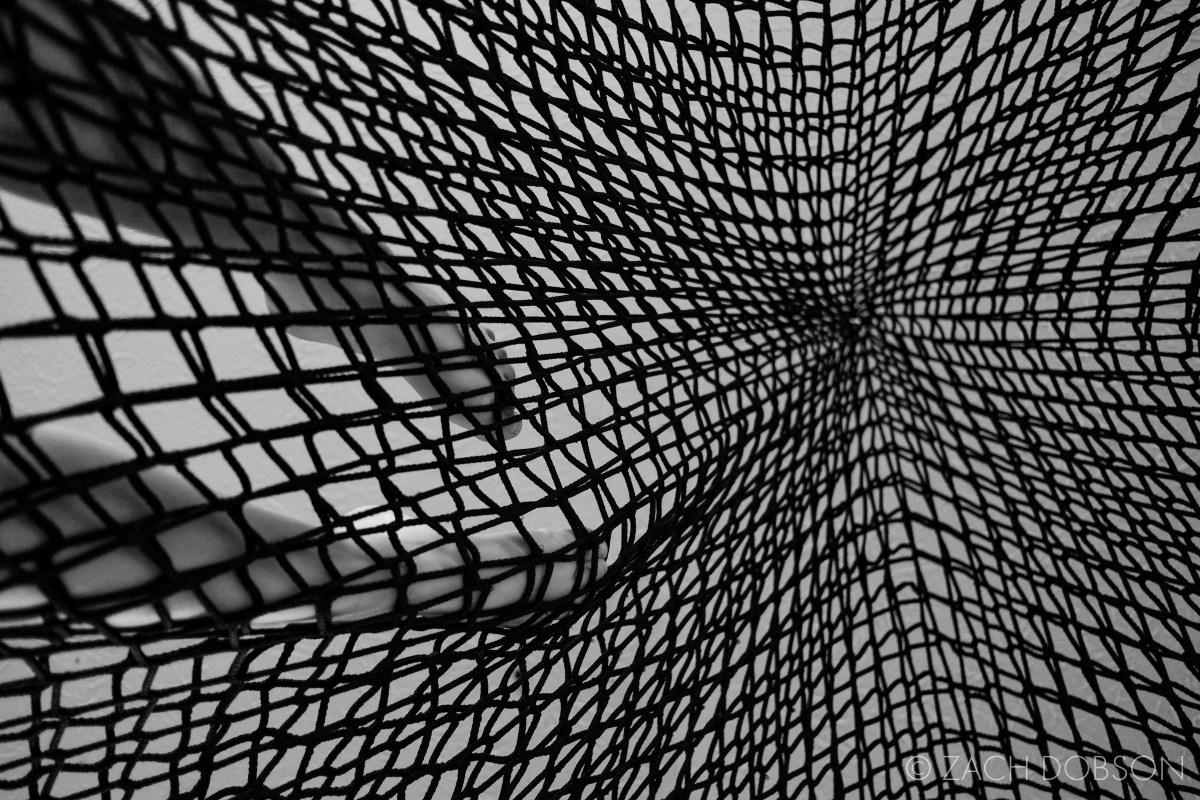 kid in climbing net in basement