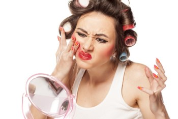 nervous woman with curlers removes makeup with her hands