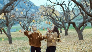 Two girls in a park throwing maple leaves up in the air