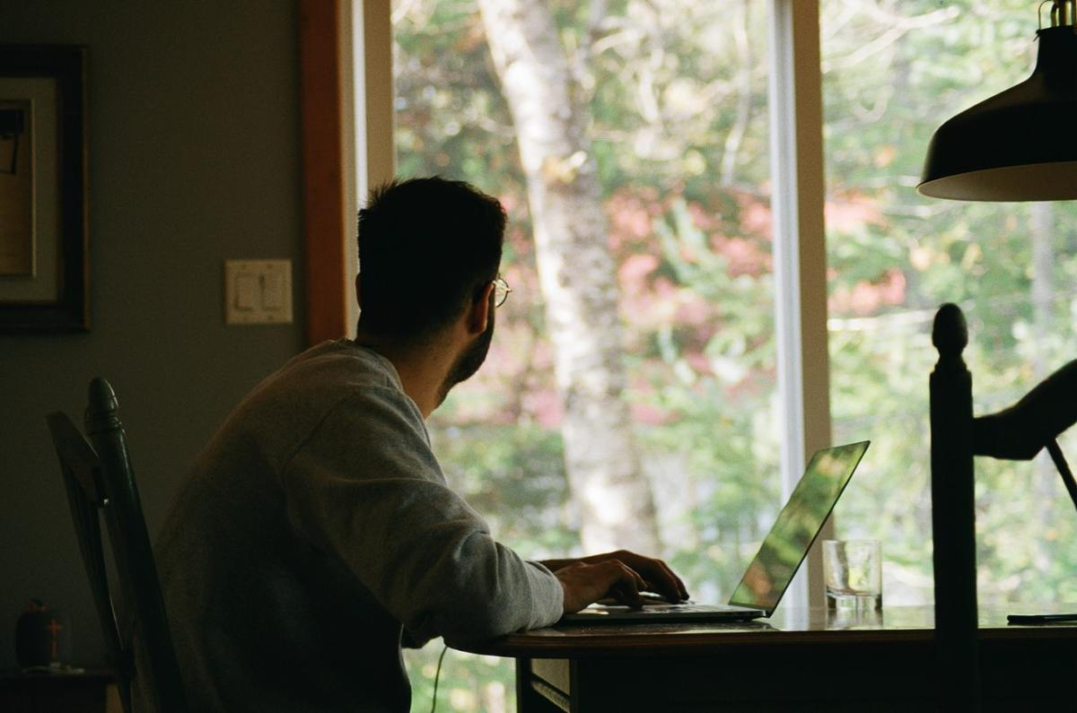 Man wearing grey t shirt looking out the window while sitting in his part time office at home on his desk with a laptop